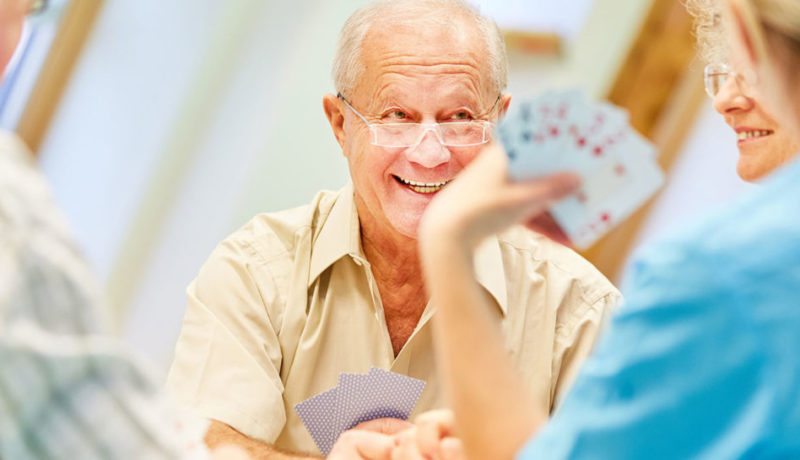seniors enjoy playing cards at assisted living community